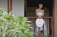 Young woman standing in balcony, holding hat, smiling - Asia Images Group