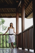 Young woman in white dress standing in balcony, looking away - Asia Images Group