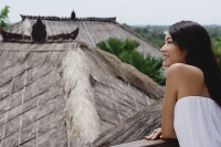 Young woman leaning on railing looking out at thatched roofs - Asia Images Group