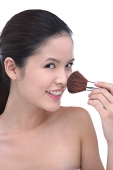 Young woman using make-up brush, looking at camera - Asia Images Group
