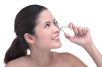 Young woman using eyelash curler - Asia Images Group