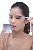 Young woman brushing eyebrows, looking at compact mirror - Asia Images Group