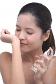 Young woman using perfume, smelling wrist - Asia Images Group