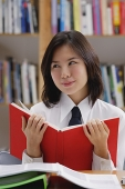 Young woman in library, holding book, looking away - Asia Images Group