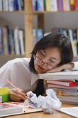 Young woman in library, sleeping on stack of books - Asia Images Group