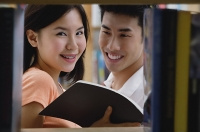 Couple in library, woman looking at camera - Asia Images Group