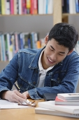 Young man in library, writing - Asia Images Group