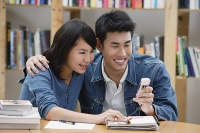 Couple in library, looking at mobile phone - Asia Images Group