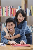 Couple in library, woman embracing man from behind - Asia Images Group