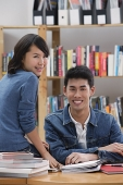 Couple in library, looking at camera - Asia Images Group