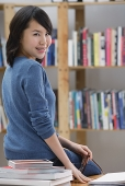 Young woman in library, sitting on table, looking over shoulder at camera - Asia Images Group