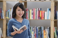 Young woman in library, holding a book looking at camera - Asia Images Group