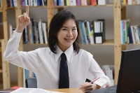 Young woman in library, hand raised, smiling - Asia Images Group
