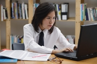 Young woman in library, using laptop, biting lip - Asia Images Group