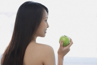 Young woman holding green apple, looking away - Asia Images Group