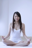 Young woman sitting in yoga position, meditating - Asia Images Group