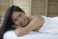 Young woman lying down on massage table, smiling at camera - Asia Images Group