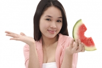 Young woman holding a slice of watermelon, looking at camera - Asia Images Group
