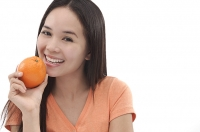 Young woman holding an orange - Asia Images Group