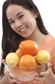 Young woman holding bowl of oranges and lemons - Asia Images Group