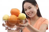 Young woman holding bowl of oranges and lemons towards camera - Asia Images Group