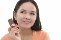 Young woman with a bar of chocolate, looking away - Asia Images Group