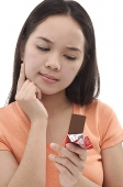 Young woman looking at a bar of chocolate, hand on chin - Asia Images Group
