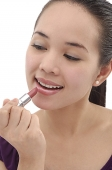 Young woman applying lipstick - Asia Images Group