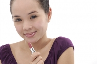 Young woman holding lipstick tube - Asia Images Group