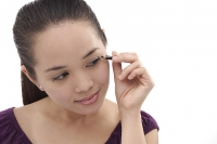 Young woman applying eyeliner - Asia Images Group