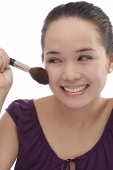 Young woman applying make-up - Asia Images Group