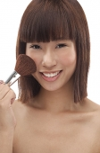 Young woman applying blusher - Asia Images Group