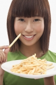 Young woman holding a plate of French fries - Asia Images Group