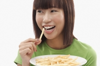 Young woman eating French fries - Asia Images Group