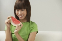 Young woman holding a slice of watermelon - Asia Images Group