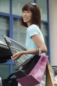 Young woman getting into car, looking at camera - Asia Images Group