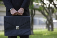Businessman holding briefcase, cropped image - Asia Images Group