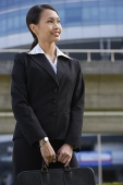 Businesswoman with briefcase, looking away - Asia Images Group