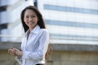 Female executive smiling at camera, hands clasped - Asia Images Group