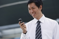 Businessman looking at mobile phone, smiling - Asia Images Group