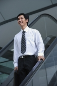 Businessman on escalator, smiling - Asia Images Group