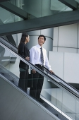Businessman and businesswoman on escalator - Asia Images Group
