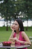 Young woman sitting at outdoor table, hand on chin, looking away - Asia Images Group