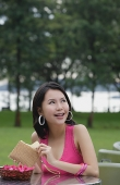 Young woman sitting at outdoor table, holding wallet, looking away - Asia Images Group