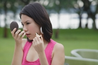 Young woman outdoors, looking at compact, applying make-up - Asia Images Group