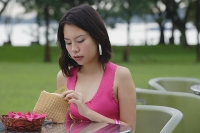 Young woman sitting at outdoor table, looking into wallet - Asia Images Group