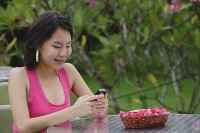 Young woman sitting at outdoor table, looking at mobile phone - Asia Images Group