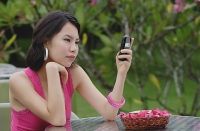 Young woman sitting at table outdoors, looking at mobile phone - Asia Images Group