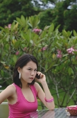 Young woman the phone, angry expression on face - Asia Images Group