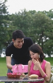 Man surprising woman with gift - Asia Images Group